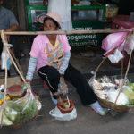 天秤棒で行商する女性が道端でたたずむ